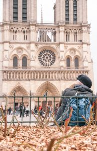 A man sits in front of Notre Dame in Paris